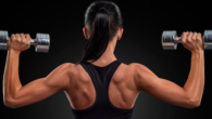 Girl standing with her back with dumbbells in each hand and showing her beautiful shoulders and arms