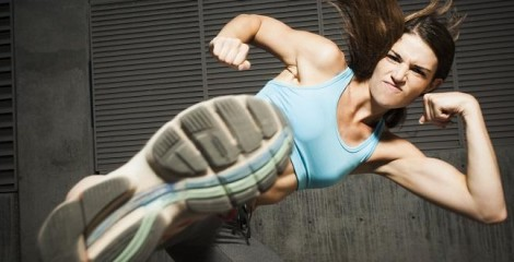 A strong and beautiful girl on the grey background does front kick with her leg showing the sole of the shoe