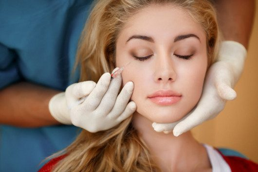 The doctor keeps syringe at girl's face before botox injection procedure