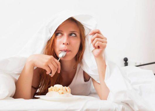 Girl with a spoon in her mouth is lying under the cover and eating a cake. Girl craving sweets because of sleep deprivation