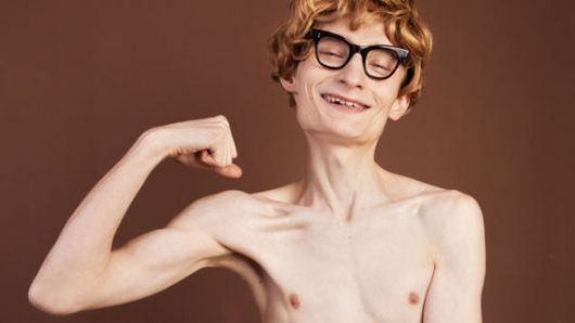 A very thin and naked guy in glasses without muscles isolated on dark flexing his biceps