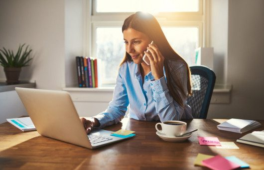 Girl is sitting at the table in front of the laptop with a cup of coffee and talking on the phone. She is working from home