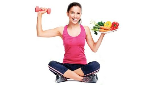 A beautiful sporty girl holding a dumbbell and a place with vegetables