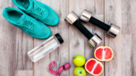 Running shoes, dumbbells, water bottle and fruit are on the wooden background