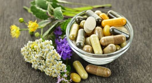 Different vitamins and dietary supplements are in the bowl on grey table with white and purple flowers