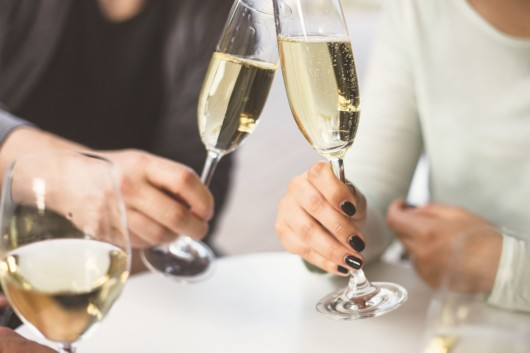 A man and a woman are sitting at the table with 2 glasses of champagne