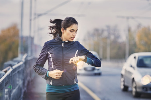 A young woman is checking her fitness watches while jogging along the road