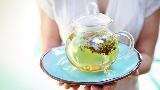 a girl holds a plate with a a transparent teapot full of green tea