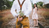 A romantic guy with flowers behind his back and the girl stands in front of him. they are both outside