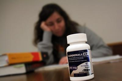 Girl is sitting at the table where there are books and adrenal pills