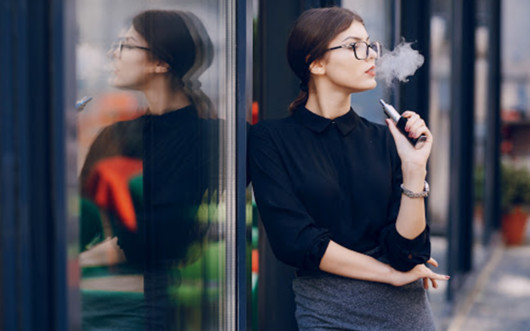 Girl in glasses vaping outside