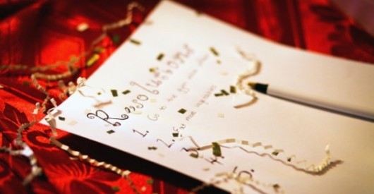 A sheet of paper on the red background with new year resolutions