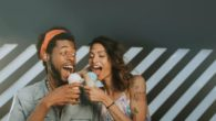 A man and a woman are having fun and eating ice cream together