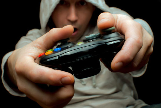 A guy in a hoody and with a gamepad on black