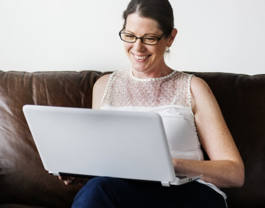 A nice girl in glasses and with a laptop is sitting on a brown sofa and smiling.