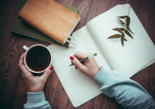 A girl is holding a pen in one hand an a cup of tea in the other one. She is going to write something in the notepad