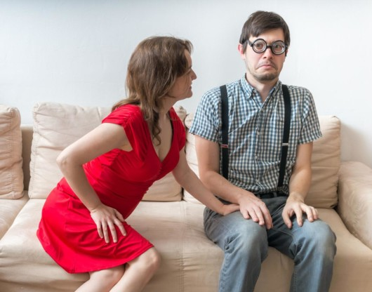 Girl in red dress is touching a shy man on the sofa