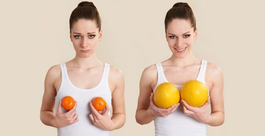 Two young girls on beige background holding small tangerines and big  oranges. Two girls imitate small and big breasts with fruits