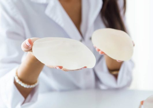 Saline or silicone filling agents are used in breast augmentation operation. The doctor is holding breast implants