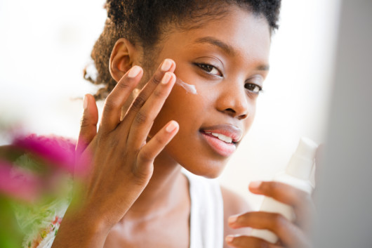 Afroamerican girl puts moisturizer on her skin as a part of skincare routine