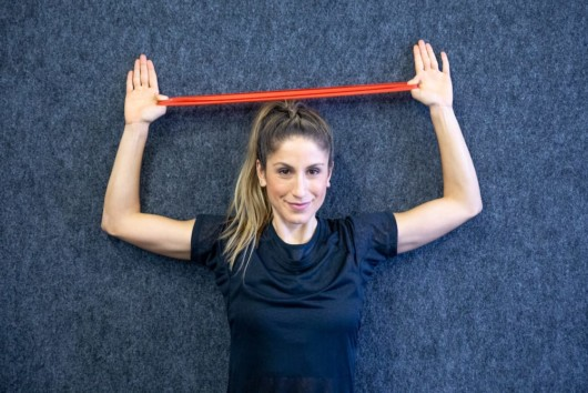 A beautiful girl in a black t-shirt on grey background is doing Resistance Band Overhead Reverse Fly .