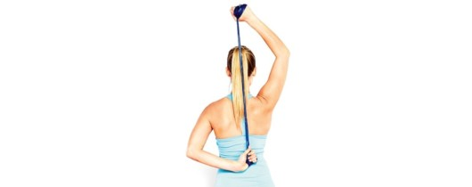 A beautiful girl in blue sport outfit on white background standing with her back to show how to do Resistance Band Overhead Triceps Extension.