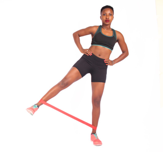 A beautiful girl in a top and shorts on white background puts her leg up to the side to shows how to do Resistance Band Side Kick