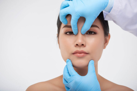 A doctor is examining the girl nose before nonsurgical rhinoplasty