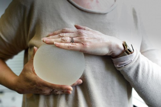 A woman is checking the size of a silicon breast implant to check if it fits her.
