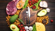 Meat, fish, avocado, greens, nuts and tomatoes with knife and fork on the wooden cutting board