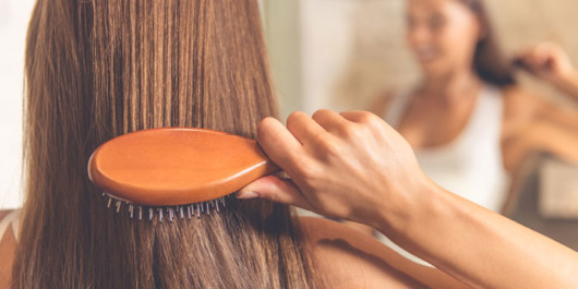 A girl is carefully brushing her dark hair in front of the mirror