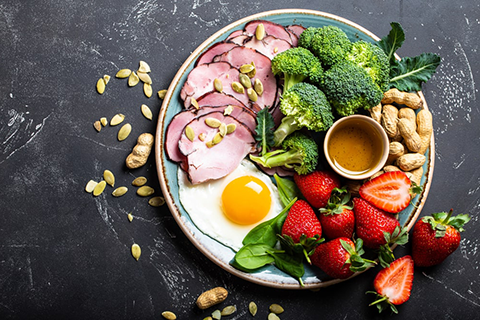Meat, seeds, broccoli, nuts, egg and strawberries ate on the plate and dark background