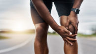 Closeup shot of a sporty man who is holding his injured knee pain while exercising outdoors