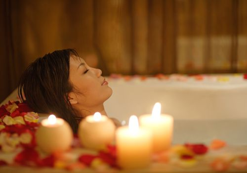 Girl is relaxing by taking aroma bath with candles