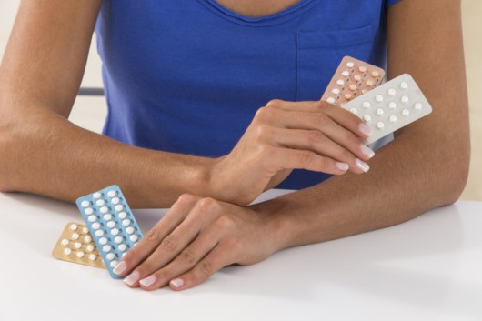 Girl holding different birth control pills and thinking which to choose