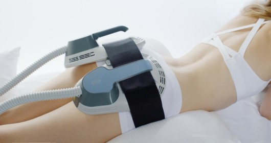 A girl is doing EmSculpt non-invasive procedure that uses focused electromagnetic energy to stimulate muscle contractions