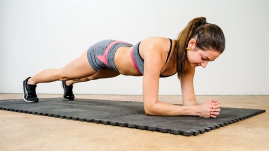 A fir girl is doing plank in the room as an isometric exercise