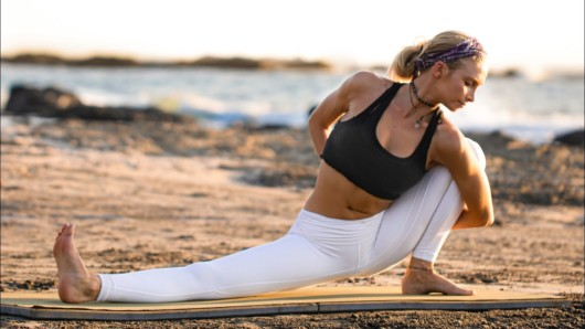 Fit girl in white leggings and black top is going yoga on the beach