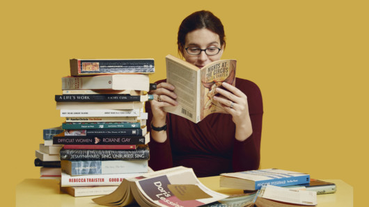 A young girl on yellow background is reading at the table with a pile of books