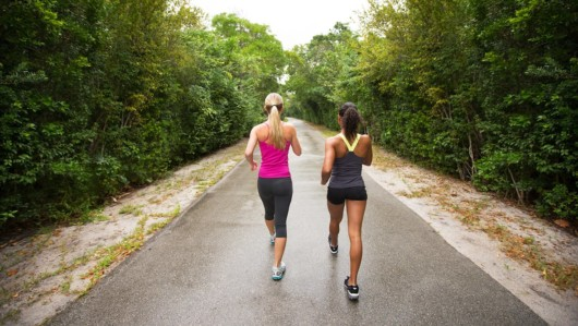 Two sporty girls in gym outfit are walking in the park.