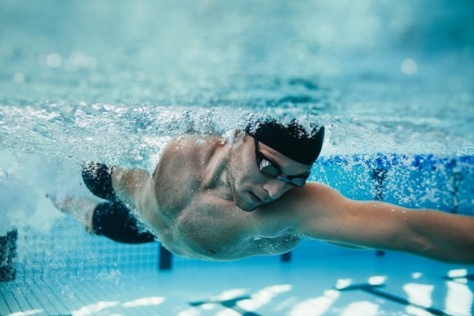 A professional swimmer is swimming in the pool
