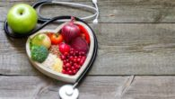 Fruits, vegetables and grains are in the white plate on wooden background next to stethoscope