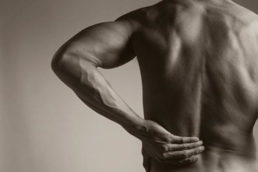 Man holds his back because of pain. He has a back strain