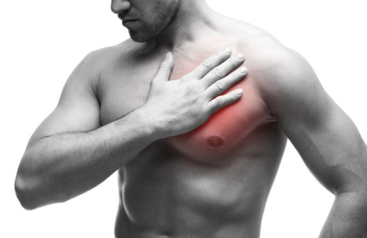 Man keeps his hand on pectoral muscles where he has the injury