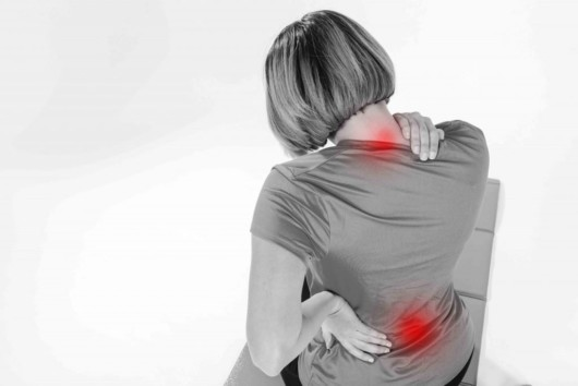 A girl on white background holds his pack in pain. She has Aslipped discin her back