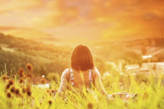 A relaxed girl is sitting with her back to the cam on the ground and overview the nature