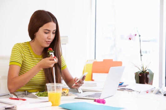 A girl is eating healthy at the table while working or studying. She eats a salad and checks her phone