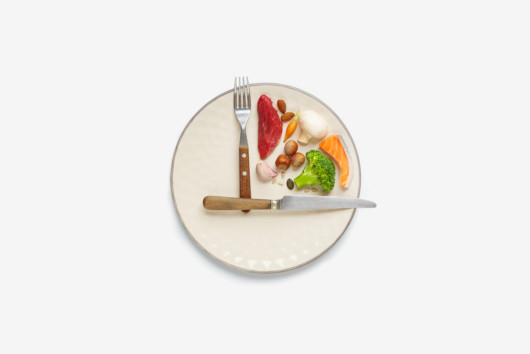 A white plate with fork and knife that show 3pm and food in between on the white background