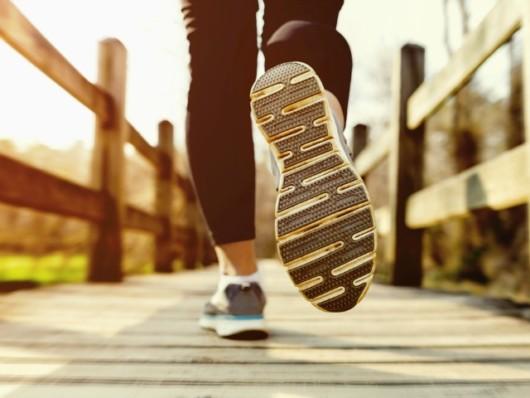 Girl is running on the wooden bridge in summer