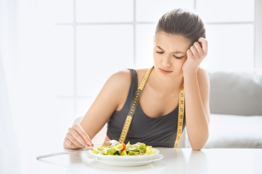 A sad girl is sitting at the white table with a measuring tape in front of the plate and not willing to eat the salad. The girl has no desire to eat the salad on the table